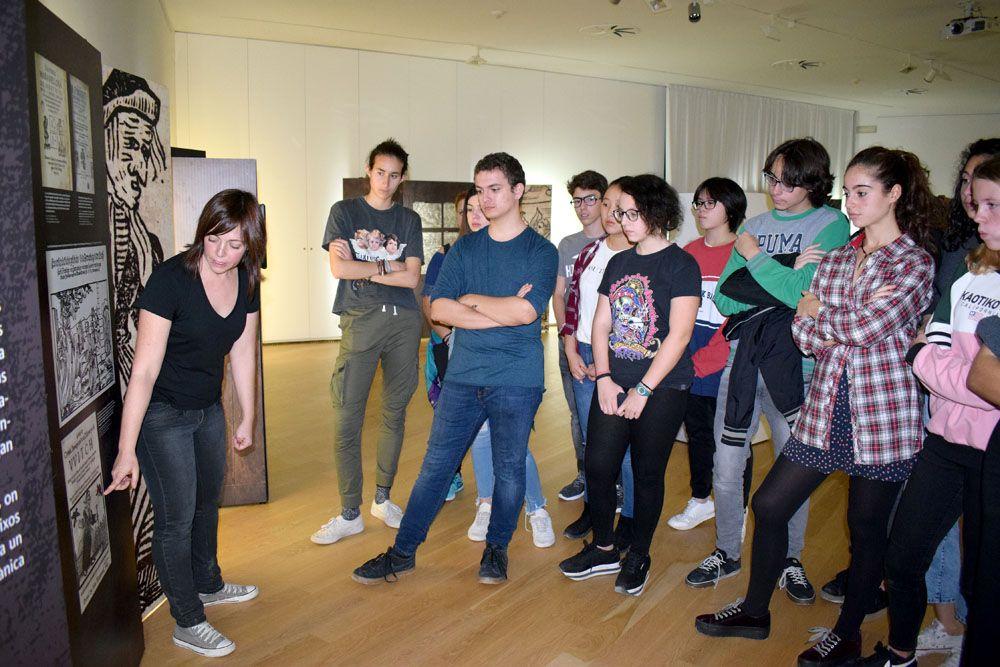 Els joves participants escolten les explicacions de la tècnica del Museu de ca n'Oliver