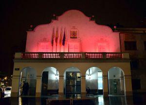 Imatge de la façana de l'ajuntament il·luminada de color rosa