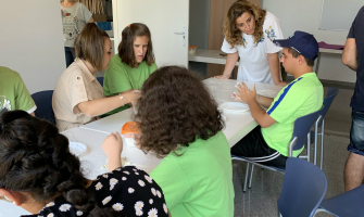 La regidora, Pepi Rivera, conversant amb un els joves participants al Casal +12