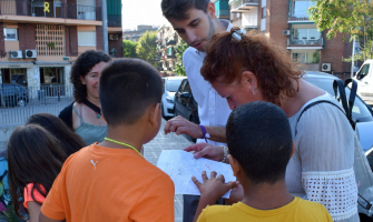 David González i Carme Arché ajudant a un grup d'infants a desxifrar el mapa
